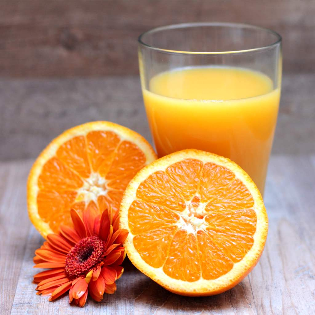 Two orange halves with a glass of orange juice and an orange gerbera flower.