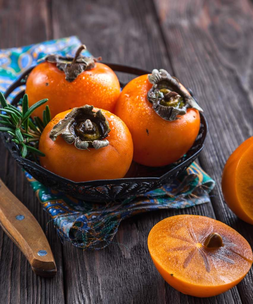 Three ripe orange persimmon fruits on a table, a fourth sliced open.