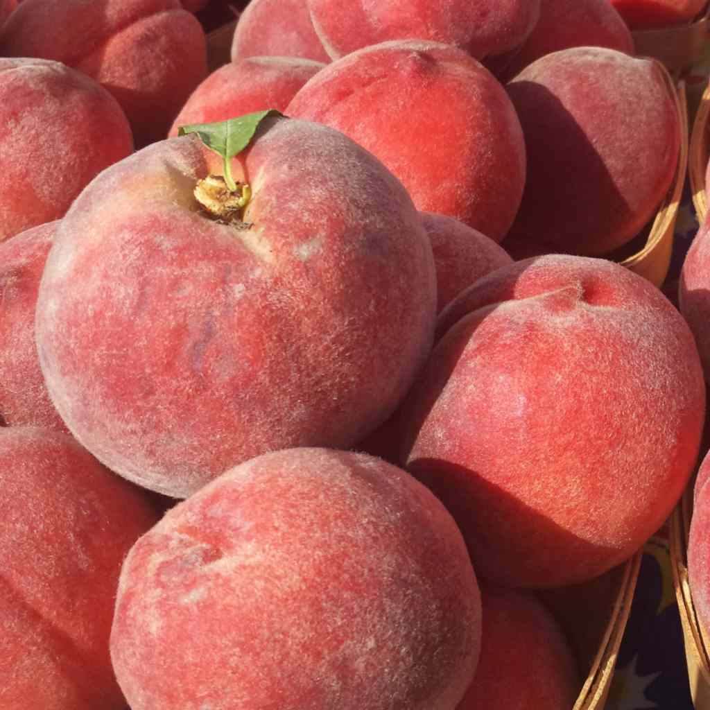 Ripe red fuzzy-skinned peaches in baskets.
